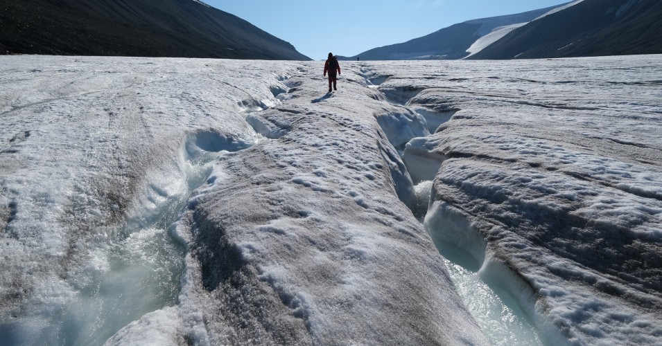 A hiker walks along winding channels carved by water on the surface of the melting Longyearbreen glacier during a summer heatwave on Svalbard archipelago on July 31, 2020 near Longyearbyen, Norway. (Photo: Sean Gallup via Getty Images)
