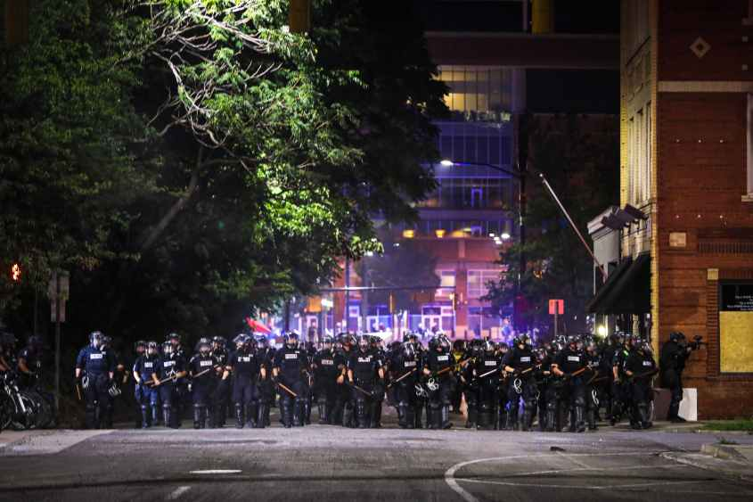 CMPD officers stand in line during a demonstration for the end of police brutaity, with The Spectrum Center behind them near uptown Charlotte, North Carolina on June 2, 2020. - US President Donald Trump said June 2, 2020, that he was now looking for a state to host the Republican National Convention later this summer, after  North Carolina said it could not do so as planned due to the coronavirus pandemic. Charlotte was the designated city to hold the Republican convention from August 24 until August 27. (Photo by Logan Cyrus / AFP) (Photo by LOGAN CYRUS/AFP via Getty Images)
