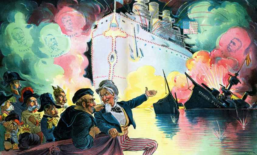 """Celebrating July 4th, 1898, """"the triumph of the American battle-ship"""" by Udo Keppler, 1872-1956, artist, 1898. Uncle Sam sitting with John Bull, who is a sailor representing England, and six figures representing """"Spain"""", """"Italy"""" (Umberto I), """"Austria"""" (Franz Joseph I), """"France"""", Germany (William II), and """"Russia"""" (Nicholas II), watching a fireworks display that shows the outline of a huge American battleship that illuminates the ruins of the """"Spanish Fleet"""", and in the clouds of smoke shows portraits of """"Schley, Sampson, Hobson and Dewey"""". (Photo by: Universal History Archive/Universal Images Group via Getty Images)"""